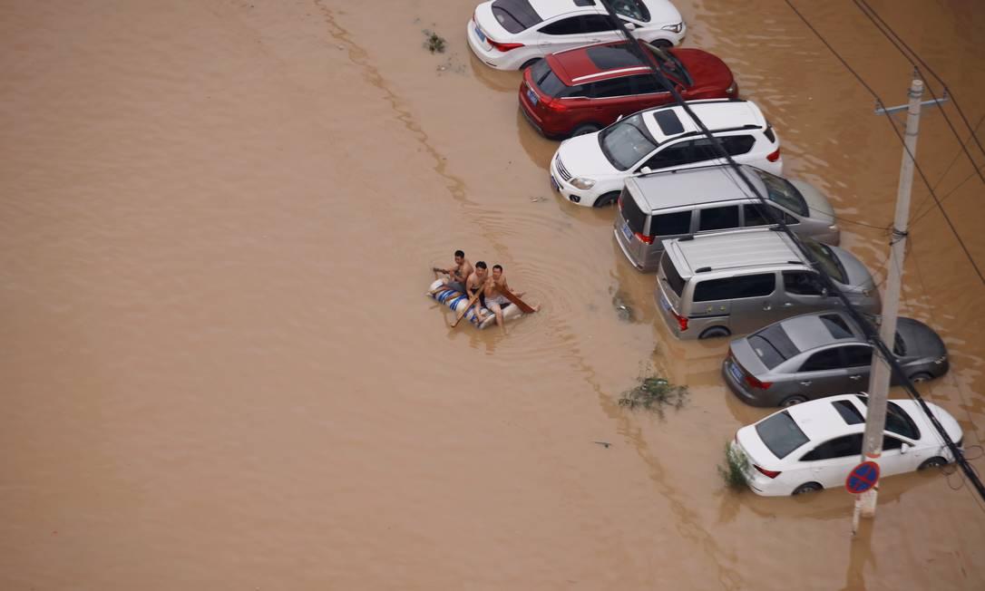 Pessoas flutuam próximas de carros imersos após chuvas e inundações em Zhengzhou, na China Foto: ALY SONG / REUTERS