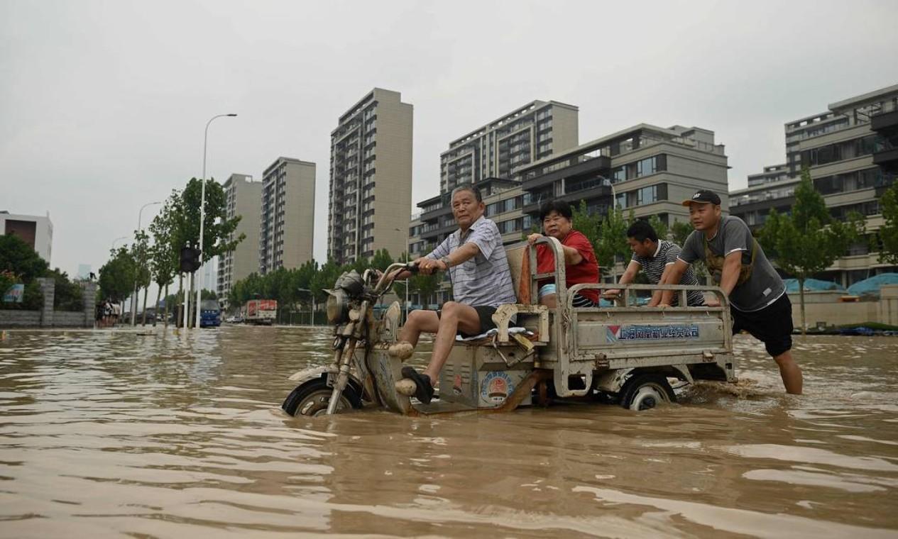 Pessoas caminham por uma rua inundada após uma forte chuva Foto: NOEL CELIS / AFP
