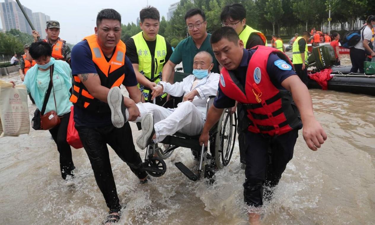 Pacietne cadeirante é carregado por equipe de resgate Foto: CHINA DAILY / REUTERS
