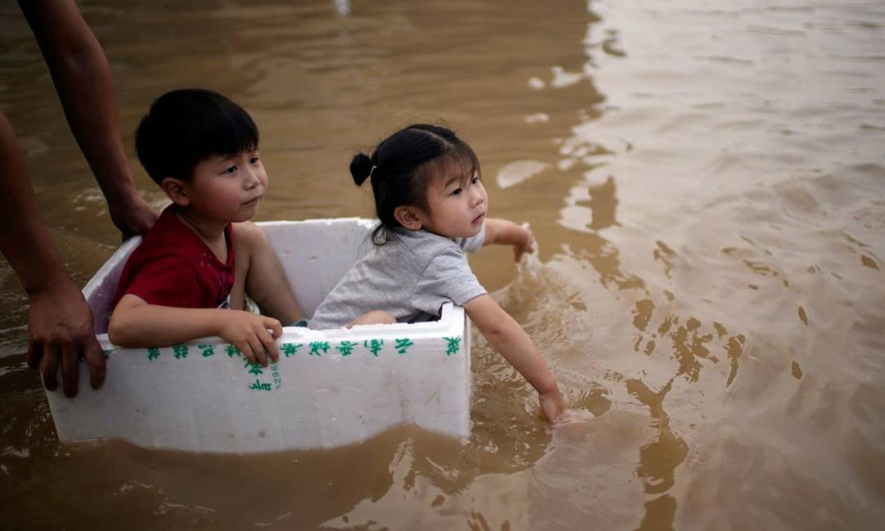 Crianaçs são levadas em caixa de isopor por rua inundada em Zhengzhou Foto: ALY SONG / REUTERS