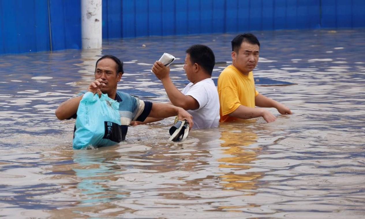 Pessoas caminham por uma estrada inundada após fortes chuvas em Zhengzhou Foto: ALY SONG / REUTERS