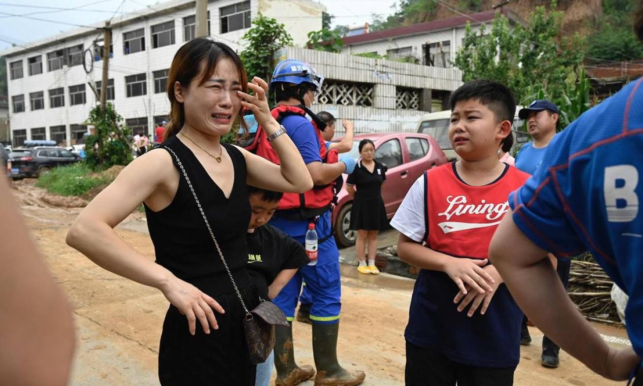 Uma mulher e um menino choram pedindo ajuda aos resgatadores depois de serem separados de seus familiares Foto: JADE GAO / AFP