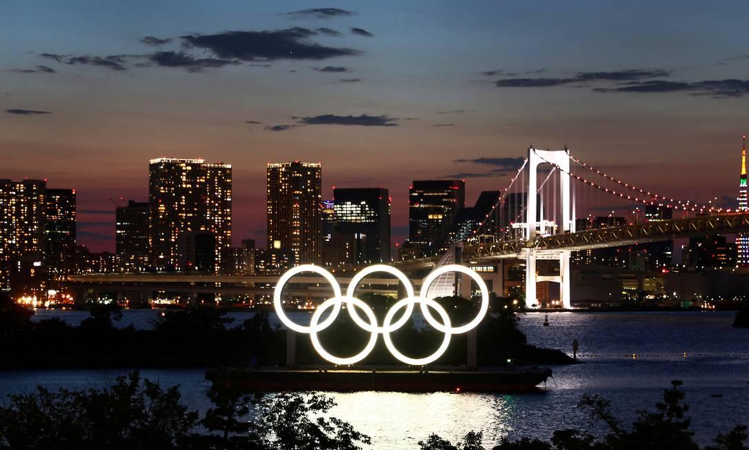 Aneis olímpicos iluminados durante o pôr do sol em Tóquio. Foto: KAI PFAFFENBACH / REUTERS