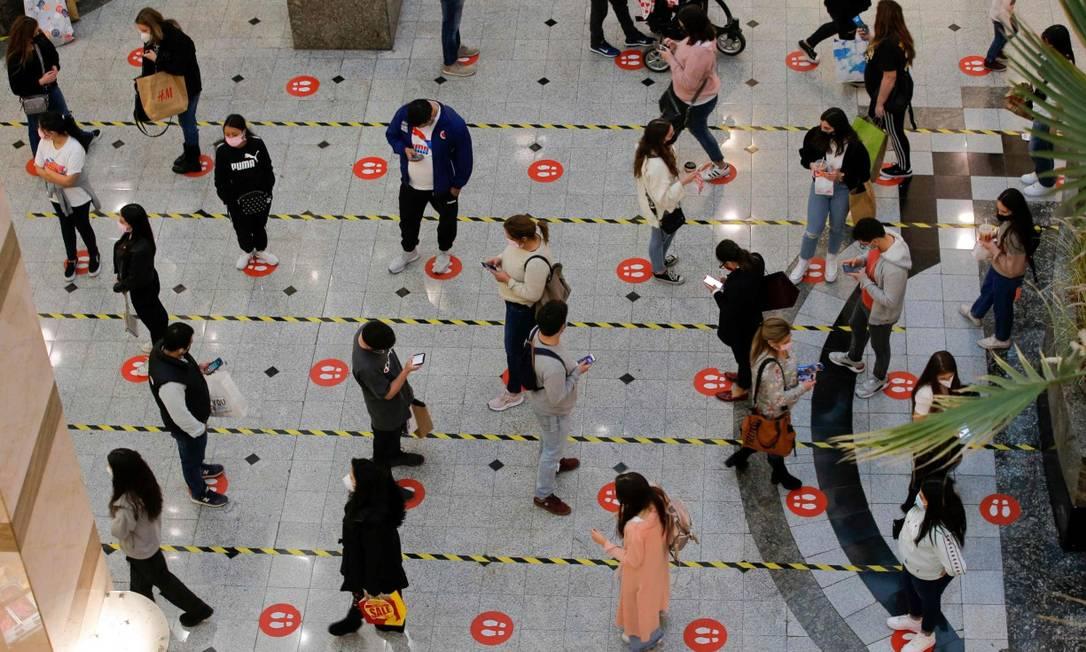Respeitando o distanciamento, pessoas fazem fila para em praça de alimentação de shopping em Santiago, no Chile Foto: JAVIER TORRES / AFP/19-7-21