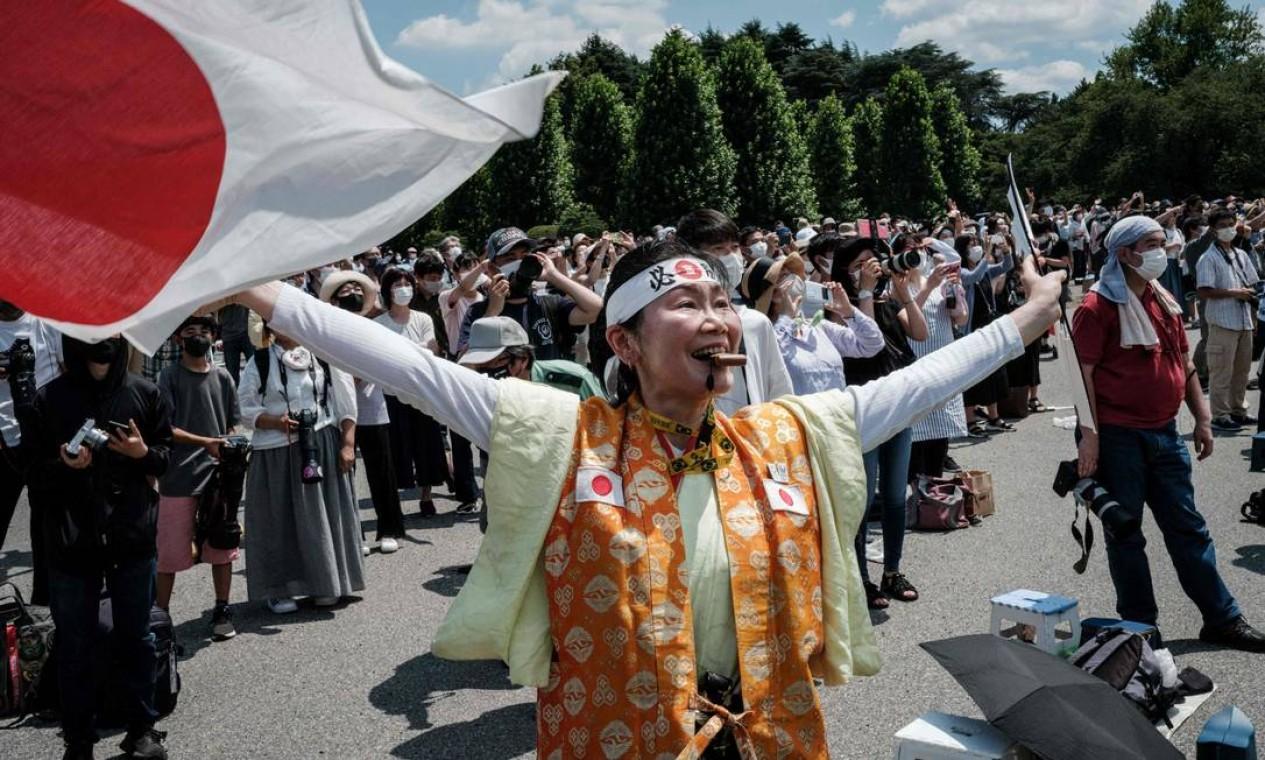 A superfã olímpica Kyoko Ishikawa, que compareceu a todas as Olimpíadas de verão nos últimos 30 anos, expressa sua gratidão enquanto Blue Impulse, equipe acrobática da Força Aérea do Japão, faz uma exibição para formar os anéis olímpicos no céus sobre Tóquio, antes da cerimônia de abertura dos Jogos Olímpicos Foto: YASUYOSHI CHIBA / AFP
