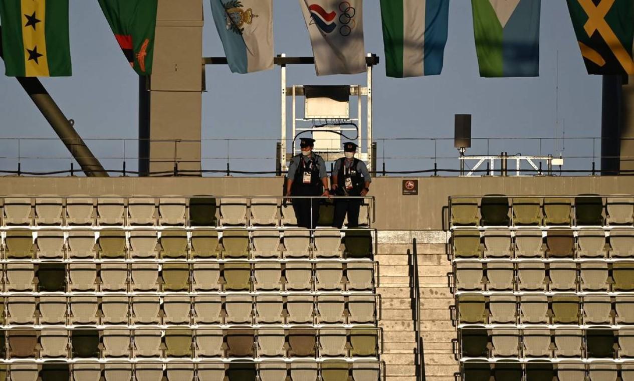 Policiais verificam a tribuna vazia antes da cerimônia de abertura dos Jogos Olímpicos de Tóquio 2020, no Estádio Olímpico, em Tóquio Foto: JEWEL SAMAD / AFP