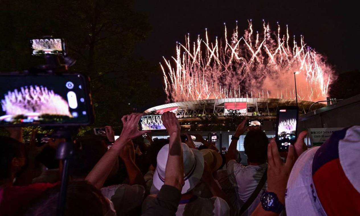 Fãs fotografam estádio olímpico do lado de fora Foto: PHILIP FONG / AFP