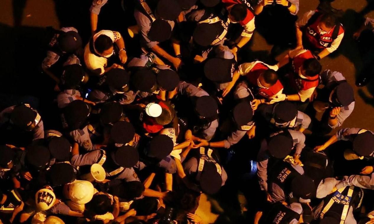 Manifestantes contra a realização dos Jogos enfrentam a polícia do lado de fora do estádio, durante a cerimônia Foto: EDGAR SU / REUTERS