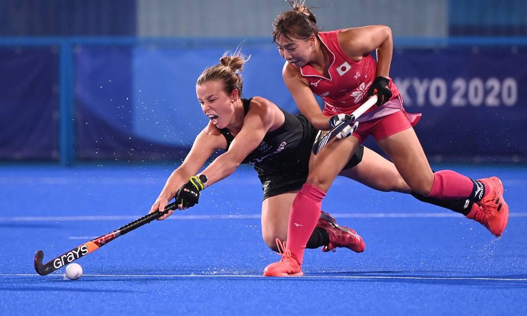 A neozelandesa Megan Hull e a japonesa Yukari Mano disputam a bola durante a partida feminina de hóquei em campo Foto: INA FASSBENDER / AFP