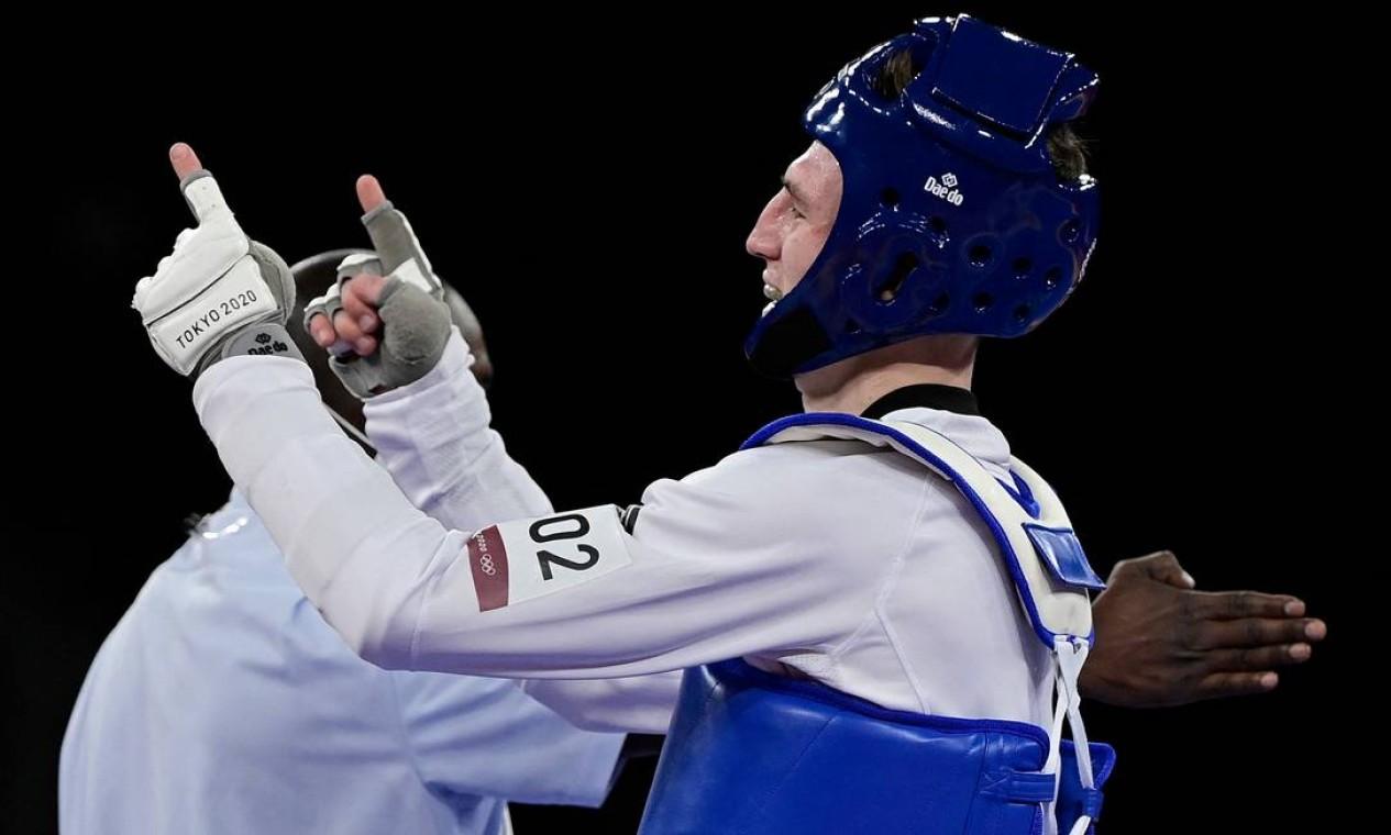 Bradly Sinden (azul), da Grã-Bretanha, comemora a vitória na semifinal masculina de taekwondo de 68 kg contra o chinês Zhao Shuai Foto: JAVIER SORIANO / AFP
