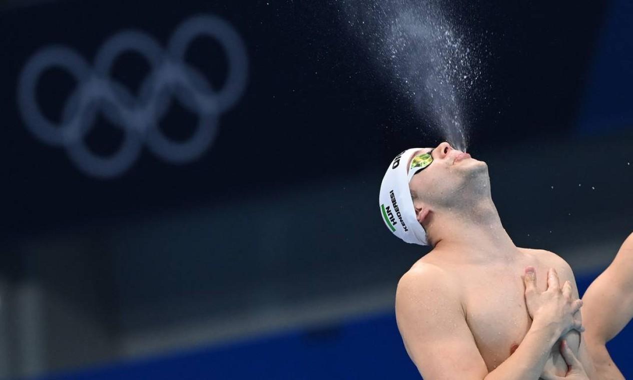O nadador húngaro Tamas Kenderesi cospindo água antes da semifinal do masculino de natação borboleta 200m Foto: ATTILA KISBENEDEK / AFP