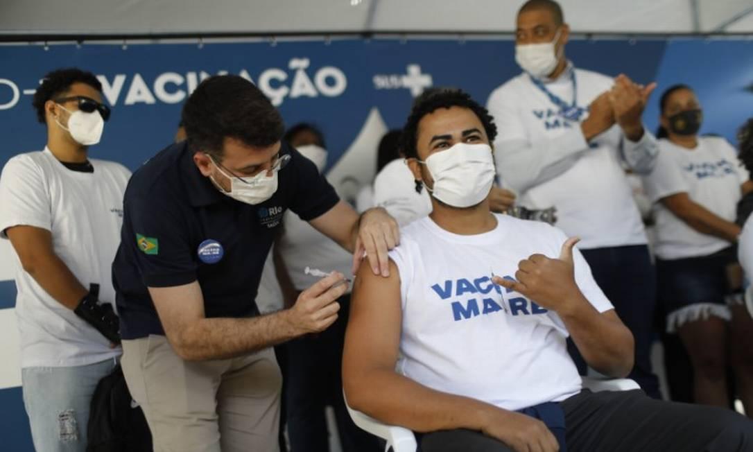Jovem é vacinado no Complexo da Maré Foto: Brenno Carvalho / Agência O Globo
