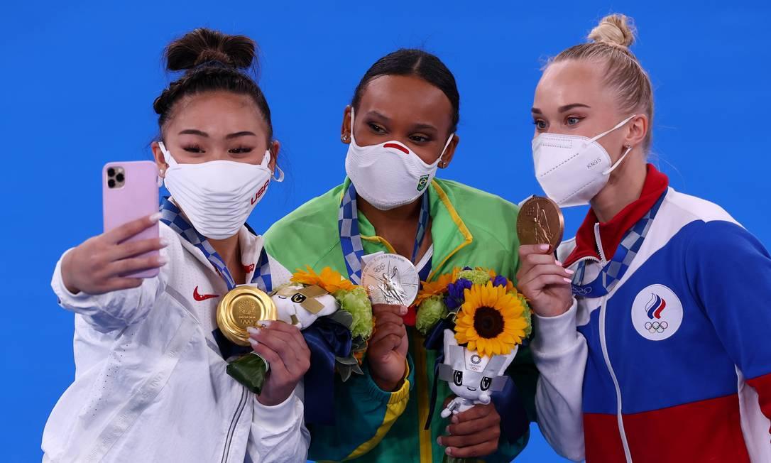 A medalhista de ouro Sunisa Lee faz selfie com Rebeca Andrade, prata, e Angelina Melnikova, bronze Foto: MIKE BLAKE / REUTERS