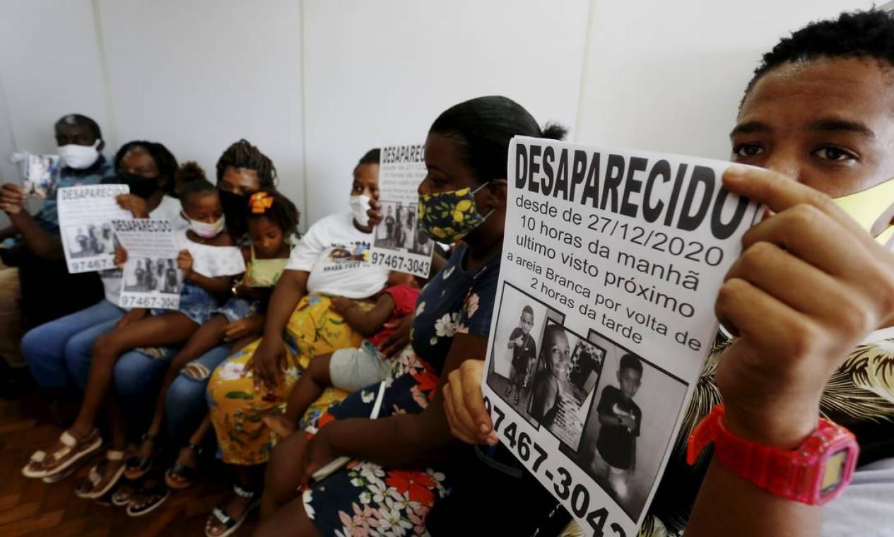 Parentes mostram cartazes com fotos das crianças: famílias criticam a investigação do caso Foto: Fabiano Rocha / Agência O Globo - 02/02/2021