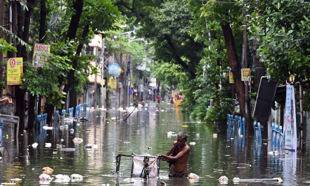 Homem empurra seu triciclo em meio a enchentes após a chuva em Calcutá, Índia Foto: DIBYANGSHU SARKAR / AFP