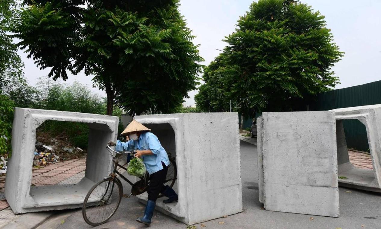 Vendedor passa por uma barricada improvisada ara impedir viagens não autorizadas em um bairro de Hanói, no Vietnã, em meio ao bloqueio do governo para impedir a disseminação da Covid-19 Foto: NHAC NGUYEN / AFP