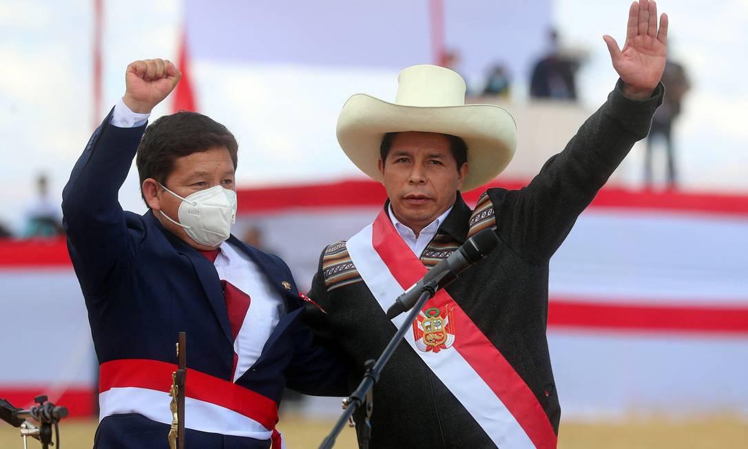 Guido Bellido (à esquerda) e o presidente peruano Pedro Castillo acenam a apoiadores durante a cerimônia simbólica de investidura presidencial em Pampa de la Quinua, em Ayacucho Foto: ERNESTO ARIAS / AFP