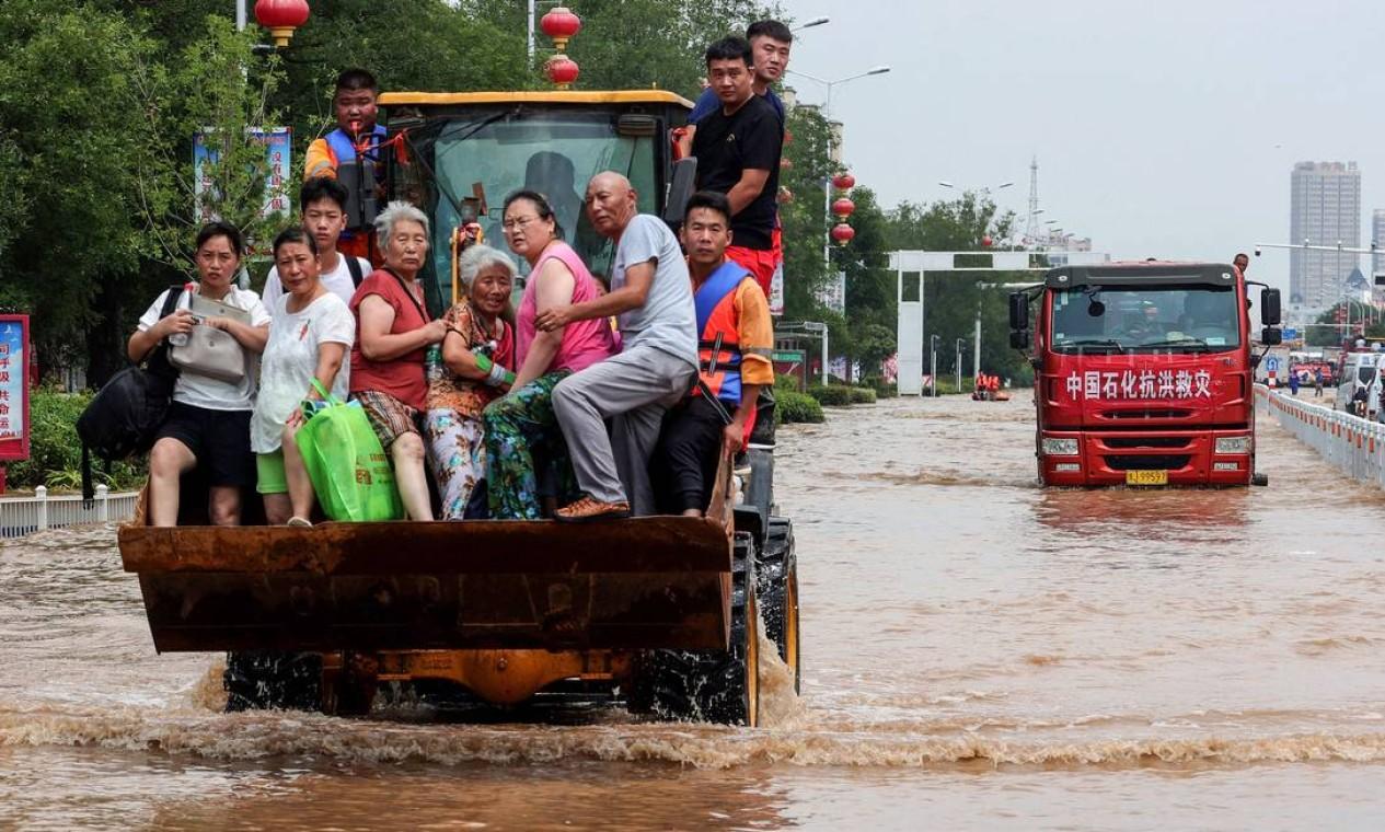 Equipes de resgate evacuam moradores de uma área inundada em Weihui, cidade de Xinxiang, na província chinesa de Henan Foto: STR / AFP
