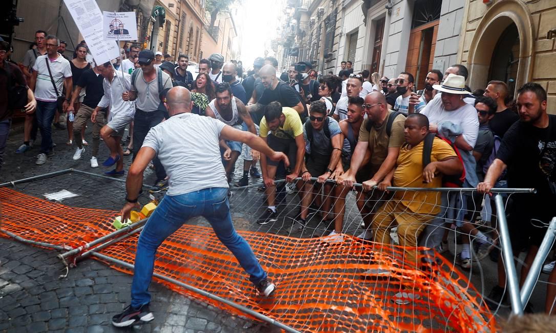 Os manifestantes removem uma barreira da polícia durante protesto contra o plano Green Pass (passe de saúde), um certificado que mostra se alguém recebeu pelo menos a primeira dose da vacina, teve teste negativo ou recentemente recuperado da Covid-19, o que será obrigatório para refeições indoor, eventos culturais e esportivos a partir da próxima semana, em Roma, na Itália Foto: GUGLIELMO MANGIAPANE / REUTERS