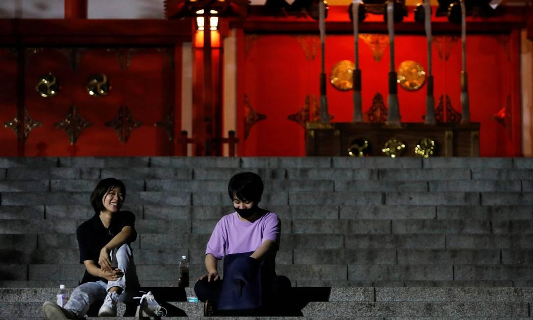 Jovens sentam e frente ao templo Hanazono Shrine após às 20h, horário em que a maoiria dos bares e restaurantes fecham em meio a surto da variante Delta da Covid-19 Foto: ANDRONIKI CHRISTODOULOU / REUTERS