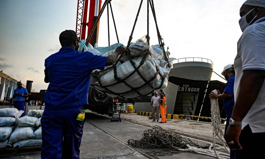Funcionário portuário descarrega carregamento de ajuda humanitária de navio mexicano, em Havana Foto: YAMIL LAGE / AFP