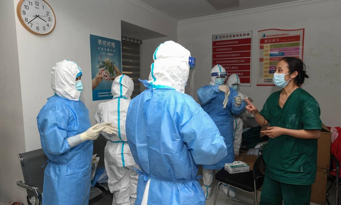 Membros da equipe médica têm uma reunião enquanto se preparam para fazer testes de ácido nucleico para verificar a presença de coronavírus em Wuhan Foto: STR / AFP