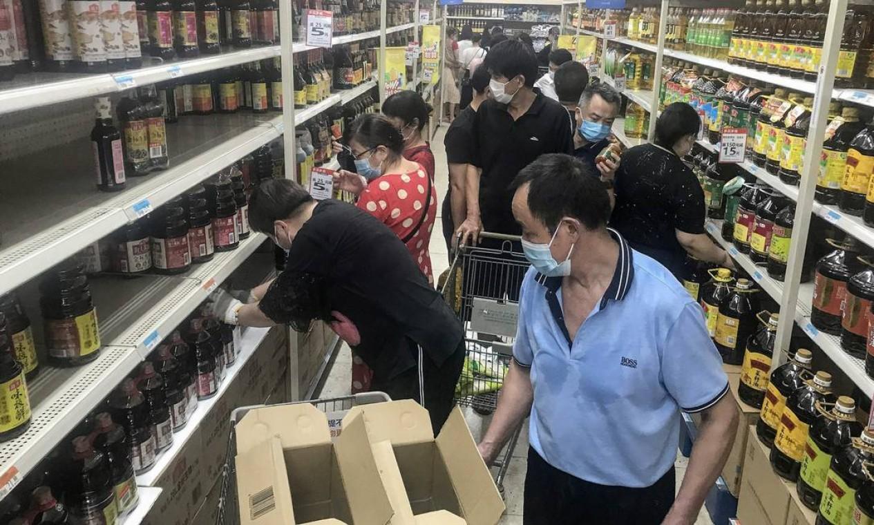 Residentes formam grandes filas em supermercado de Wuhan, na China, após a confirmação de novos casos de Covid-19 Foto: STR / AFP