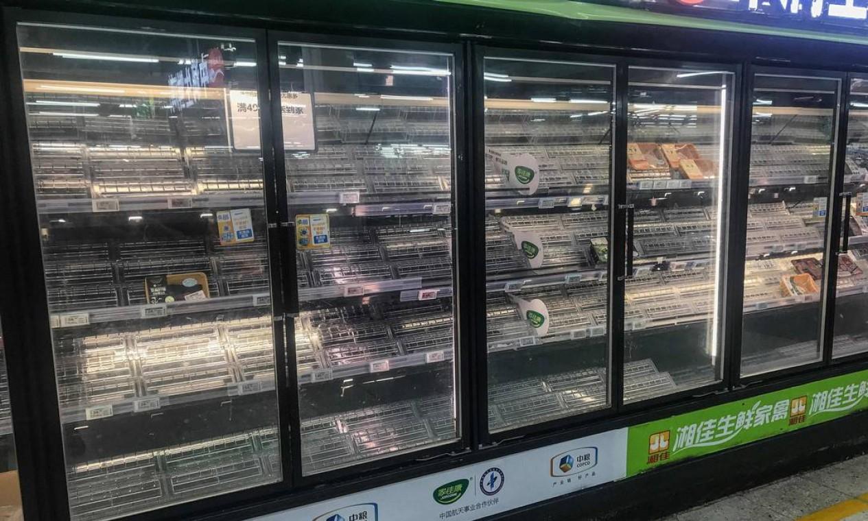 Desabastecimento: prateleiras ficam vazias enquanto as pessoas compram itens em um supermercado em Wuhan com medo de novo surto da doença Foto: STR / AFP