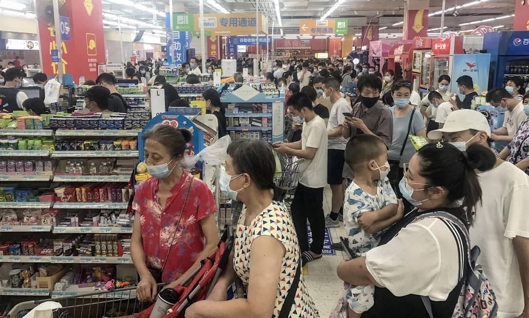 Grandes filas, carrinhos de compras lotados e prateleiras vazias. Cenas comuns no início da pandemia estão de volta à rotina de Wuhan Foto: STR / AFP
