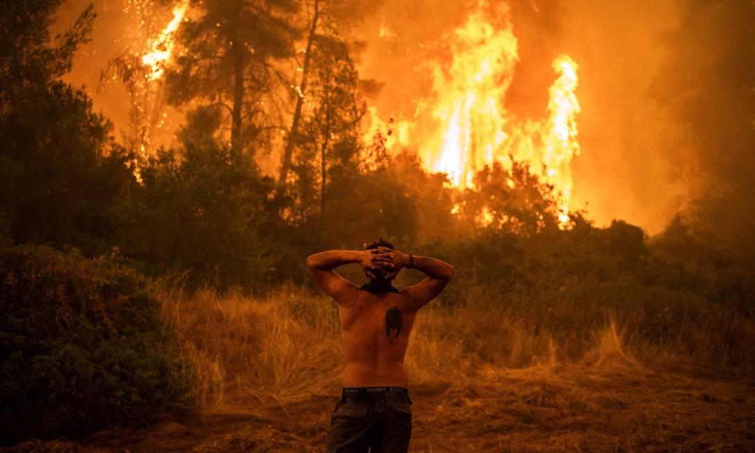 Morador lamenta incêndio na ilha de Eubeia, Grécia Foto: ANGELOS TZORTZINIS / AFP