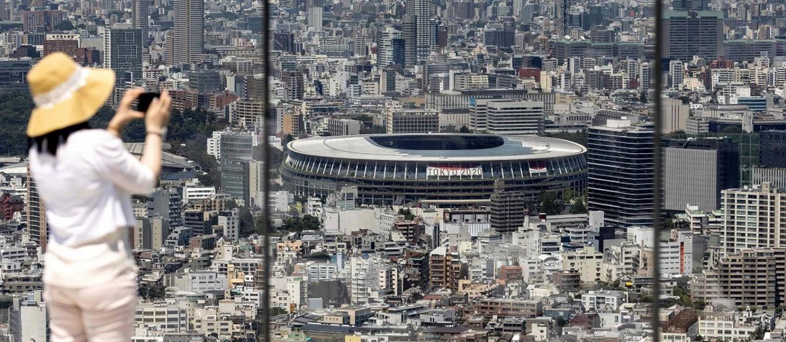 Uma mulher fotografa o Estádio Nacional de Tóquio, um dos palcos das Olimpíadas de 2020, do alto do mirante Shibuya Sky Foto: BEHROUZ MEHRI / AFP