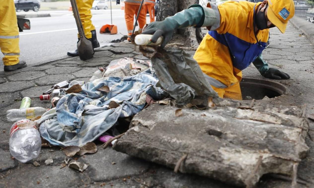 Servidor da Comlurb entra em bueiro para tirar resíduos sólidos Foto: Luiza Moraes / Agência O Globo