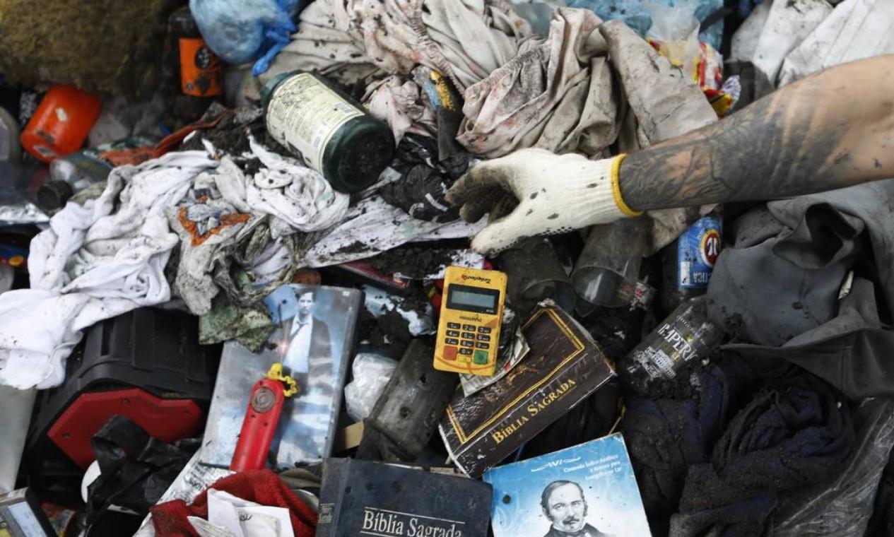 Embalagens de cerveja, Bíblia sagrada, livro espírita, maquininha de cartão são retirados de bueiros. Em 7 meses, 81 mil toneladas de resíduos são removidas de vias pela prefeitura Foto: Luiza Moraes / Agência O Globo