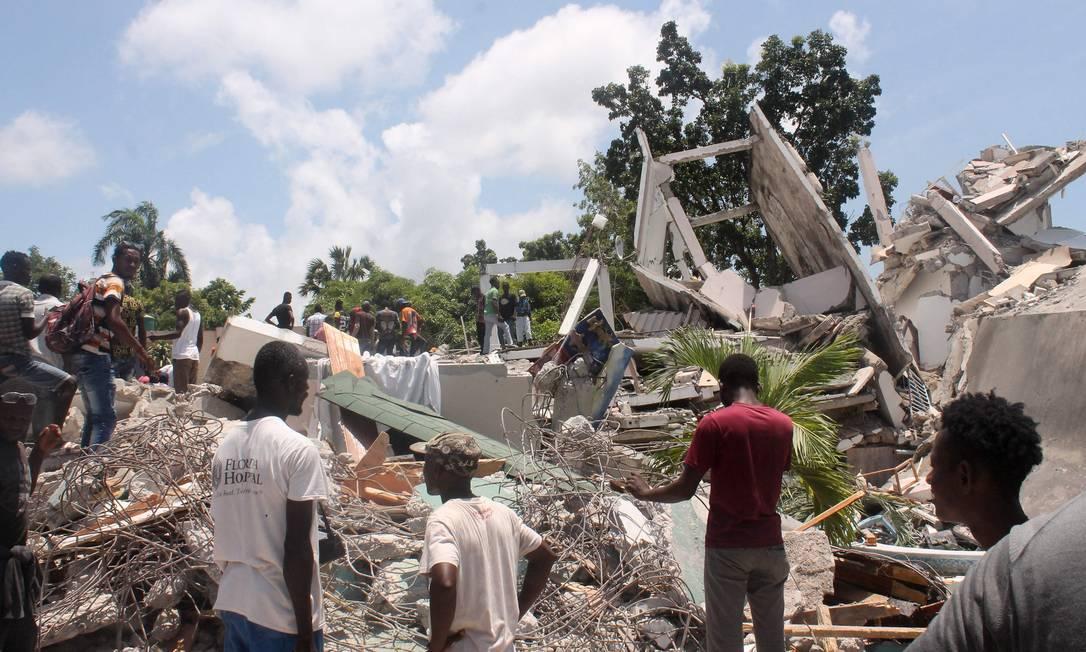 Pessoas vasculham os escombros do Manguier Hotel após o terremoto ocorrido em Les Cayes, sudoeste do Haiti Foto: STANLEY LOUIS / AFP