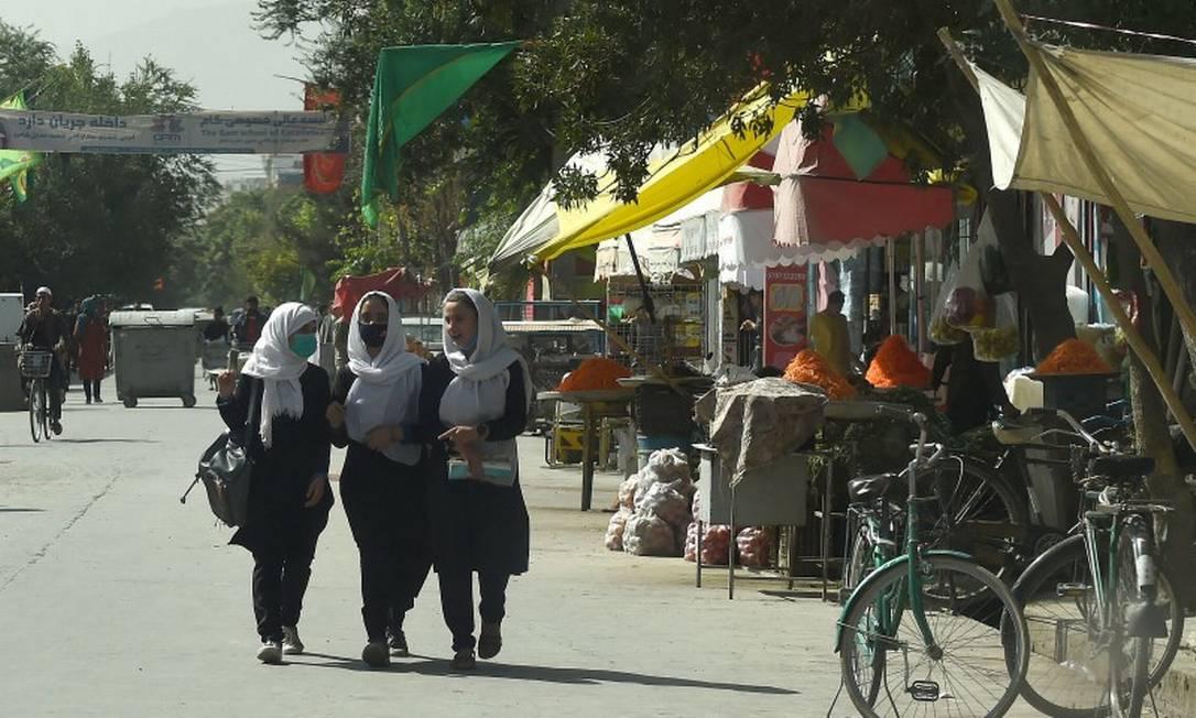 Meninas de uma escola afegã passam por uma rua em Cabul neste domingo Foto: WAKIL KOHSAR / AFP
