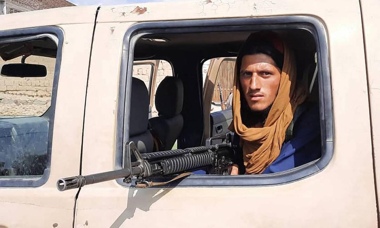 Soldado do Talibã põe arma para fora de um veículo do Exército afegão em estrada na província de Laghman Foto: - / AFP