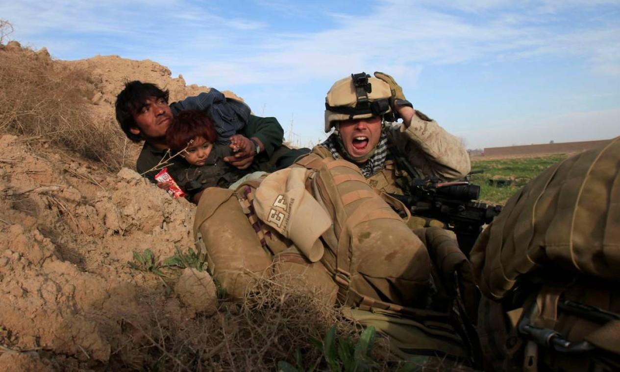 Militar da Marinha dos EUA tenta proteger afegão com o filho durante confronto com Talibã, no distrito de Nad Ali, província de Helmand, Afeganistão Foto: GORAN TOMASEVIC / REUTERS - 13/02/2010