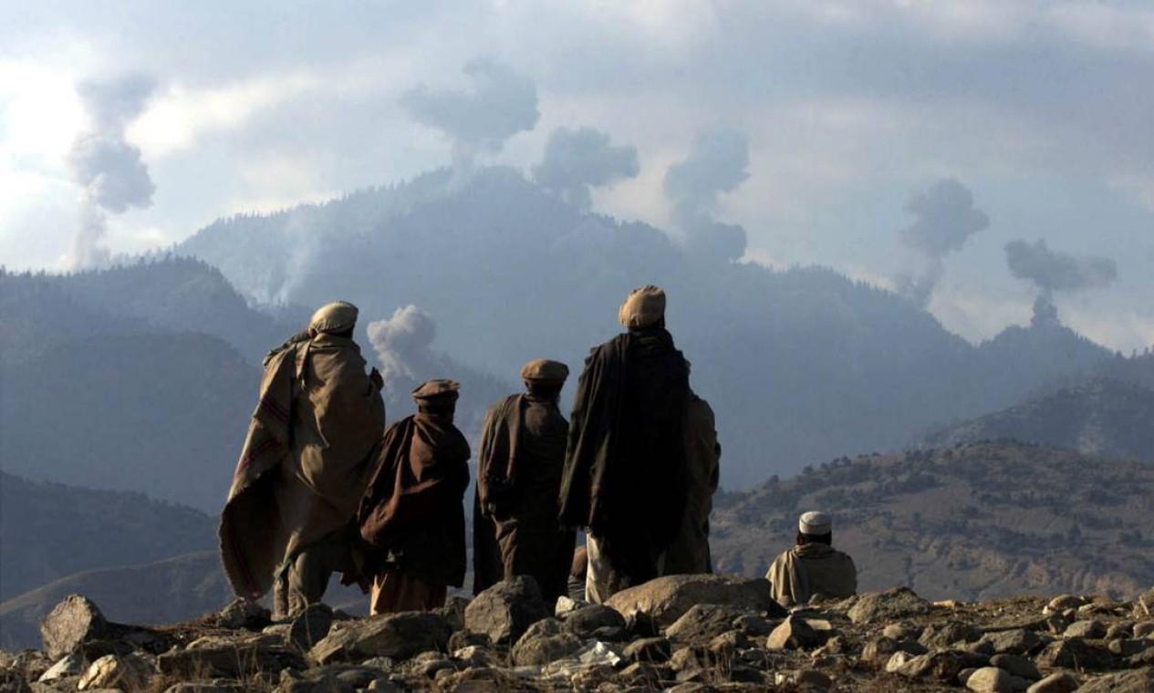 Soldados afegãos assistem a várias explosões de bombardeios dos EUA nas montanhas Tora Bora, no Afeganistão Foto: ERIK DE CASTRO / REUTERS - 16/12/2001