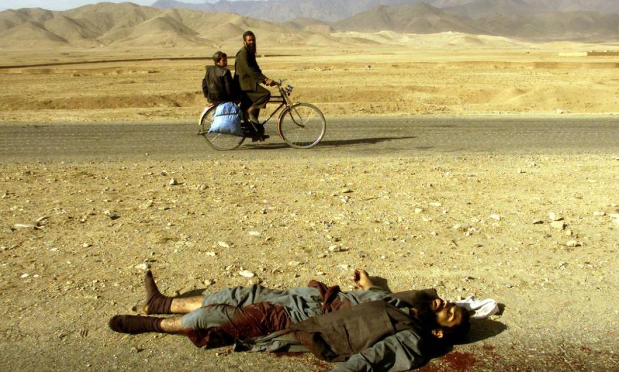 Afegão e filho passam de bicicleta pelo corpo de um talibã morto durante confronto no norte de Cabul Foto: YANNIS BEHRAKIS / REUTERS - 13/11/2001