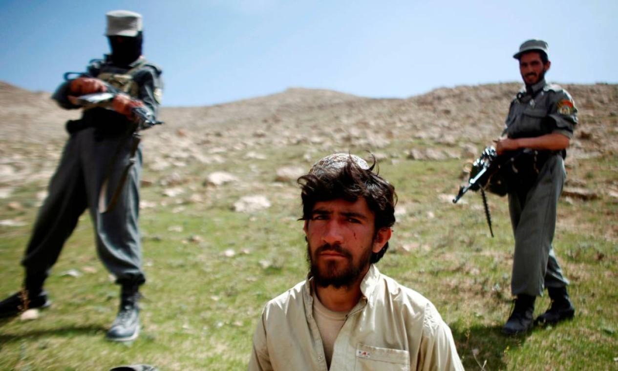 Policiais afegãos capturam talibã após tiroteio perto da vila de Shajoy, na província de Zabol Foto: Goran Tomasevic / REUTERS - 22/03/2008