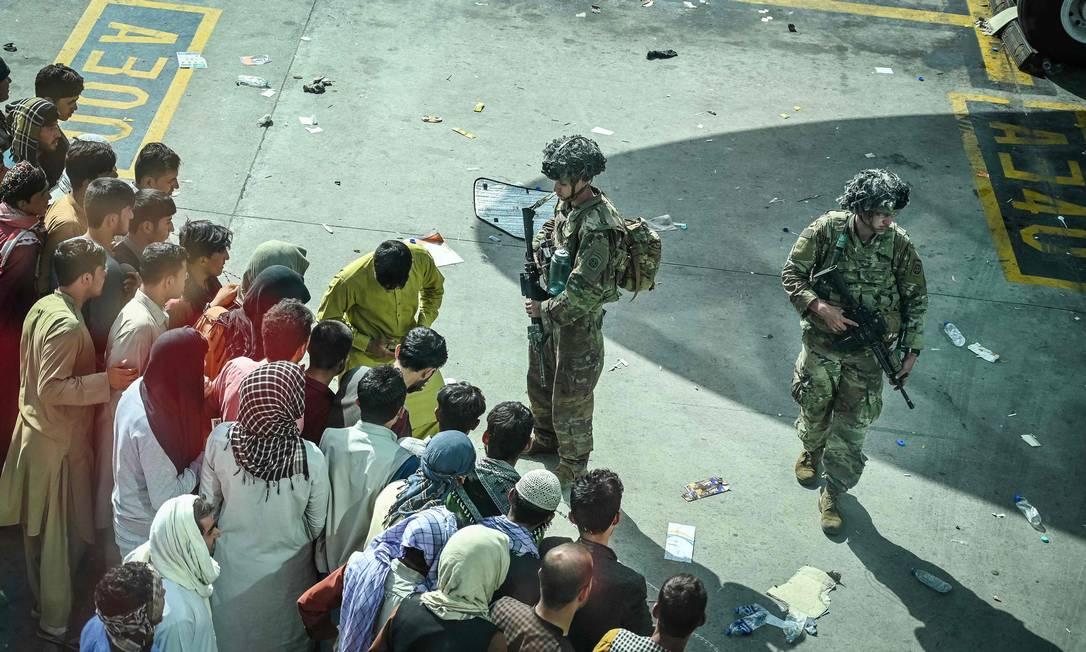Soldados dos EUA montam guarda enquanto o povo afegão espera chance de embarcar em voo de fuga Foto: WAKIL KOHSAR / AFP