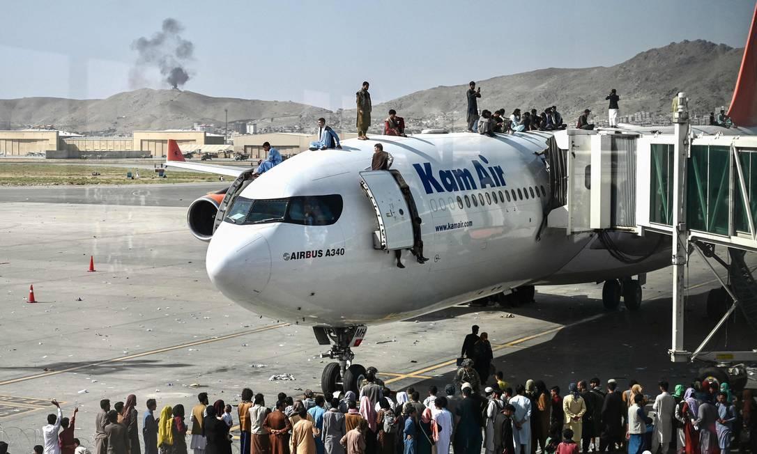 Afegãos sobem em avião comercial para tentar escapar após Talibã retornar ao poder quase 20 anos após invasão americana Foto: WAKIL KOHSAR / AFP