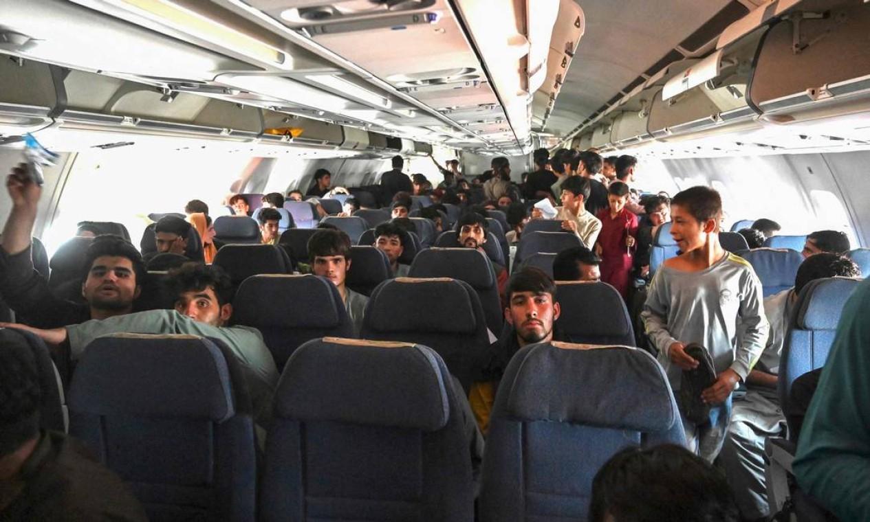 Passageiros afegãos sentam-se dentro de um avião enquanto esperam para deixar o aeroporto de Cabul Foto: WAKIL KOHSAR / AFP