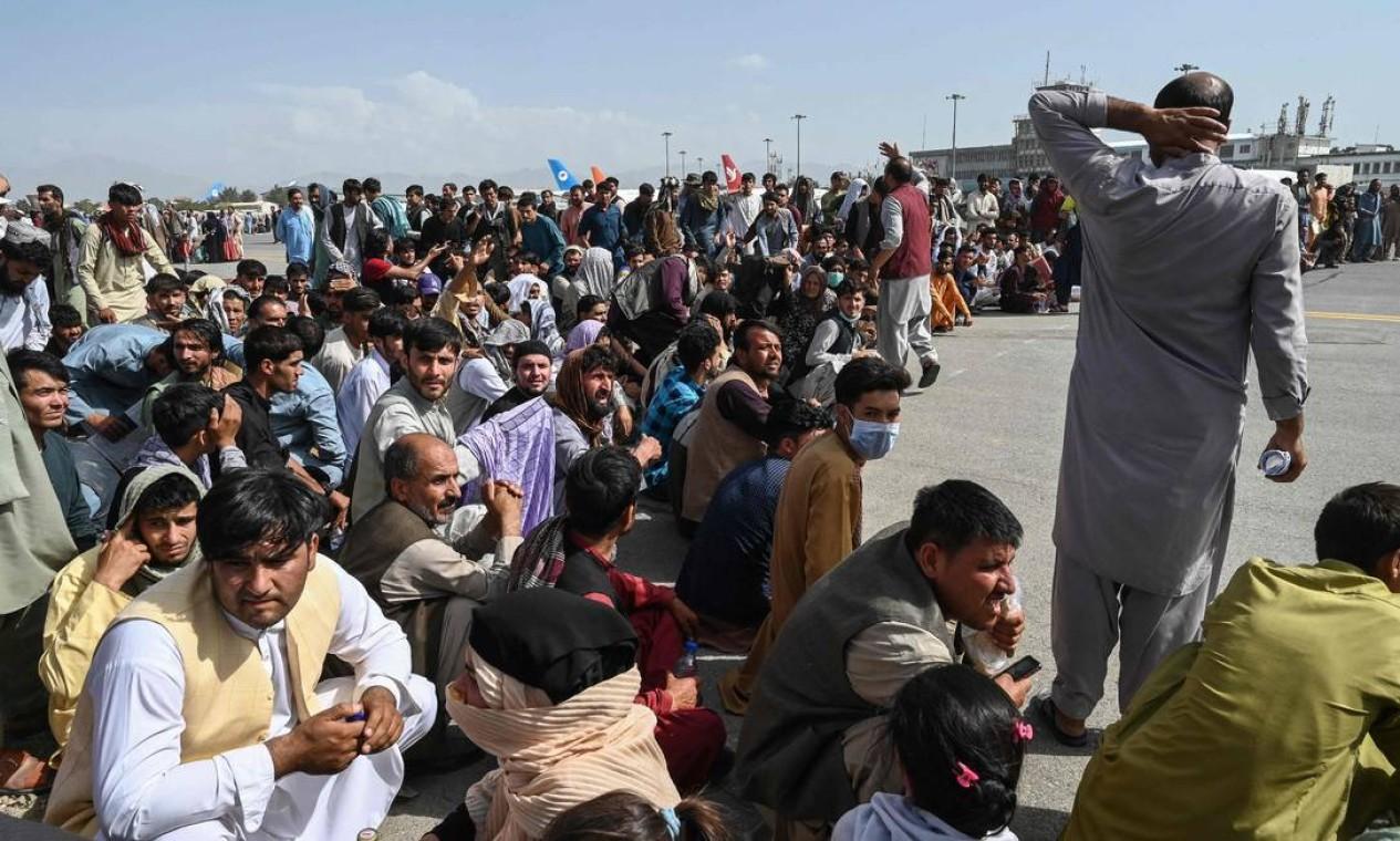 Passageiros afegãos ocupam a pista do aeroporto de Cabul em tentativa de fugir do país Foto: WAKIL KOHSAR / AFP