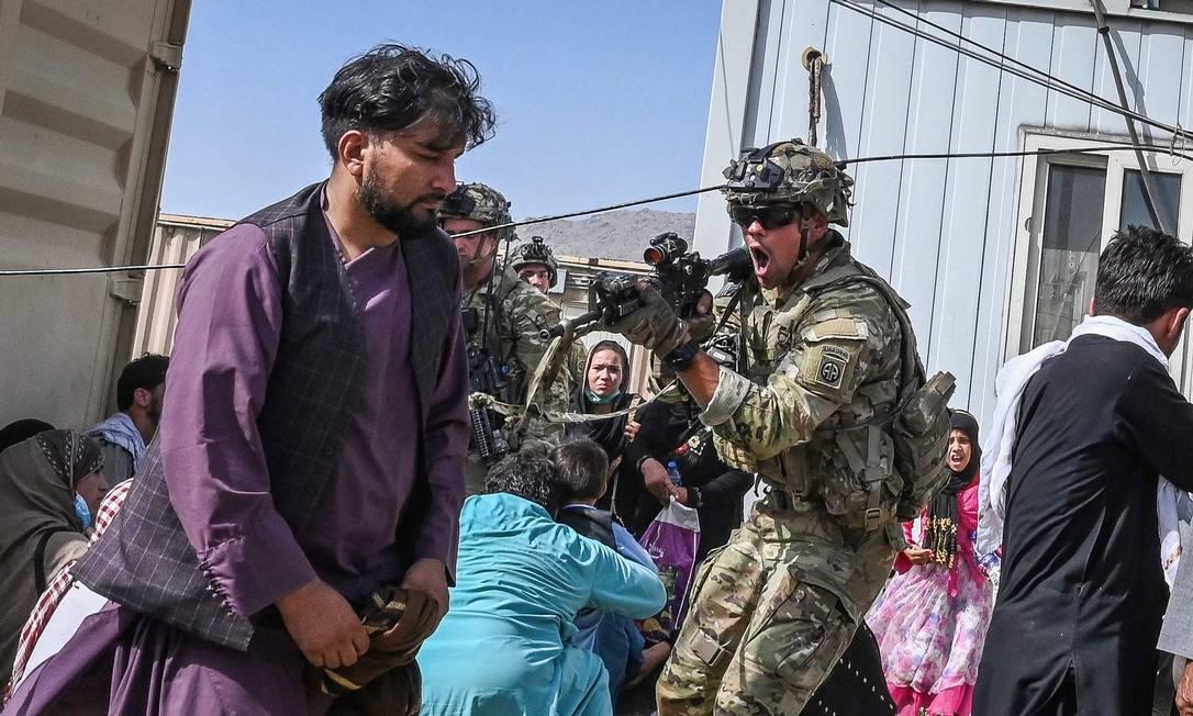 Soldado dos EUA aponta arma para passageiro afegão no aeroporto de Cabul Foto: WAKIL KOHSAR / AFP