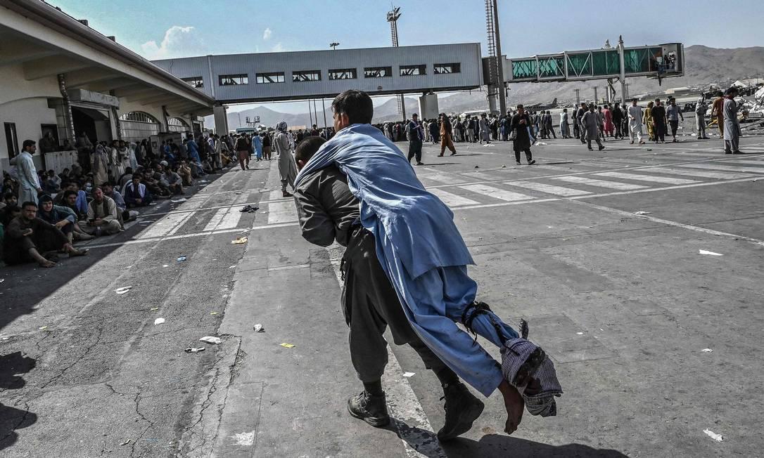 Voluntário carrega homem ferido, enquanto pessoas que esperam para tentar fugir do Afeganistão observam Foto: WAKIL KOHSAR / AFP
