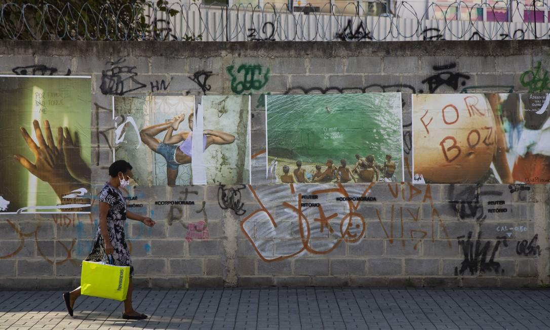 Mulher passa por lambe-lambes de fotógrafos da periferia em rua da Gamboa Foto: Leo Martins / Agência O Globo