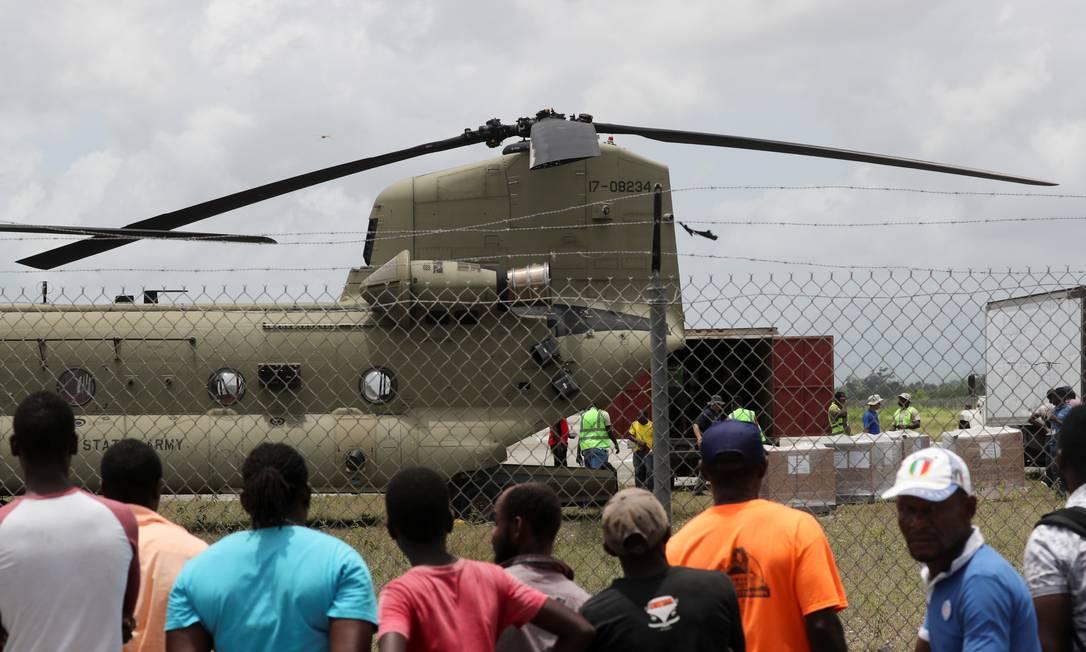 Moradores observam enquanto os trabalhadores recebem ajuda humanitária de um helicóptero dos EUA no aeroporto de Les Cayes, no Haiti Foto: HENRY ROMERO / REUTERS