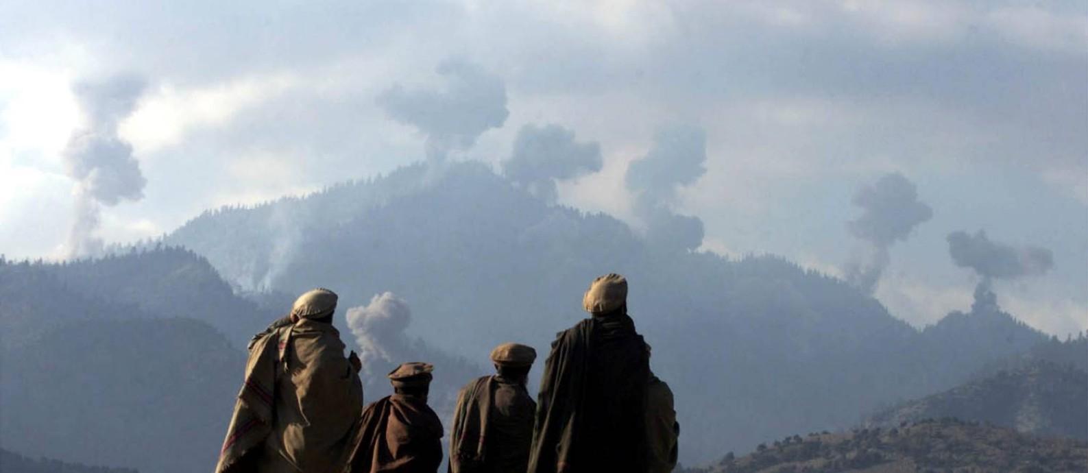 Milicianos que lutavam contra o Talibã observam bombardeio americano nas montanhas de Tora Bora, no Afeganistão, em dezembro de 2001 Foto: ERIK DE CASTRO / REUTERS