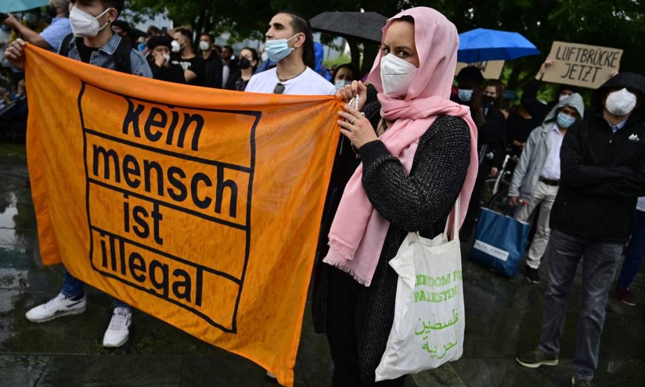 """Manifestantes exibem uma faixa com os dizeres """"Ninguém é ilegal"""" em uma demonstração de apoio ao povo afegão, em frente à Chancelaria em Berlim, Alemanha Foto: JOHN MACDOUGALL / AFP"""